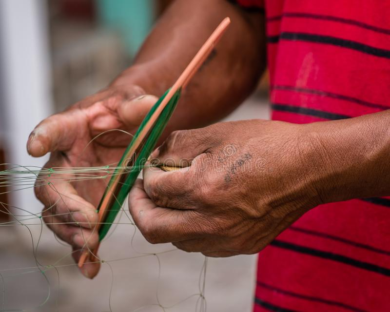 Mains travaillant à un filet de pêche dans Huanchaco, Pérou photo libre de droits