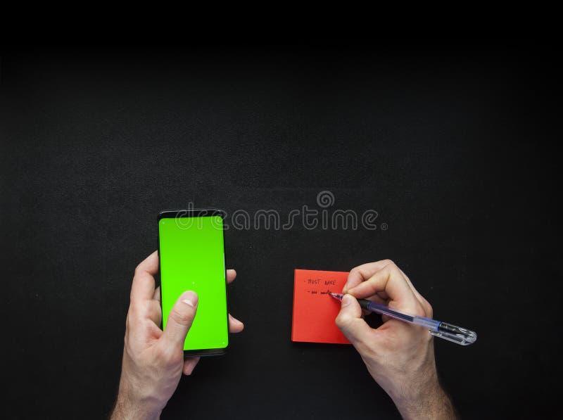 Mains utilisant le téléphone intelligent et noter vers le bas sur les notes collantes photos stock
