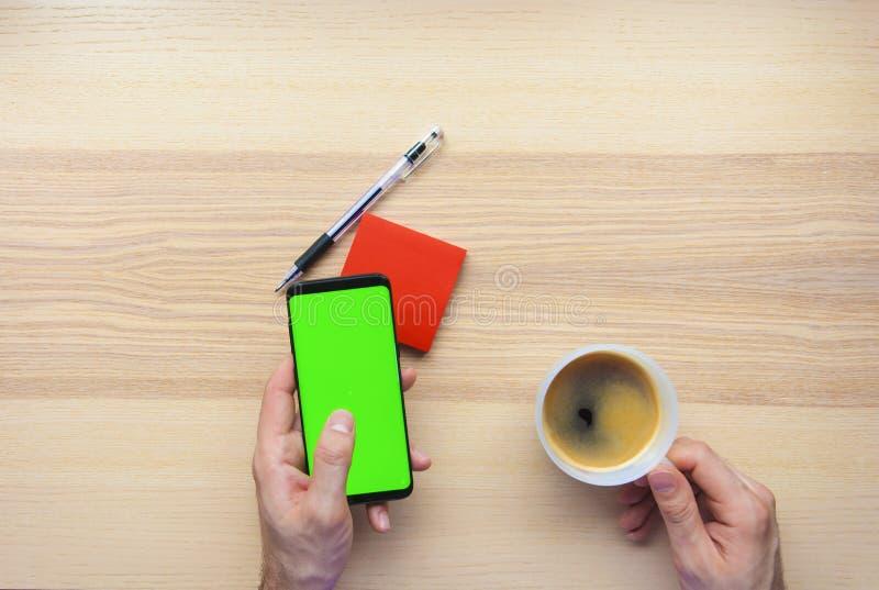 Mains utilisant le téléphone intelligent et noter vers le bas sur les notes collantes photo libre de droits
