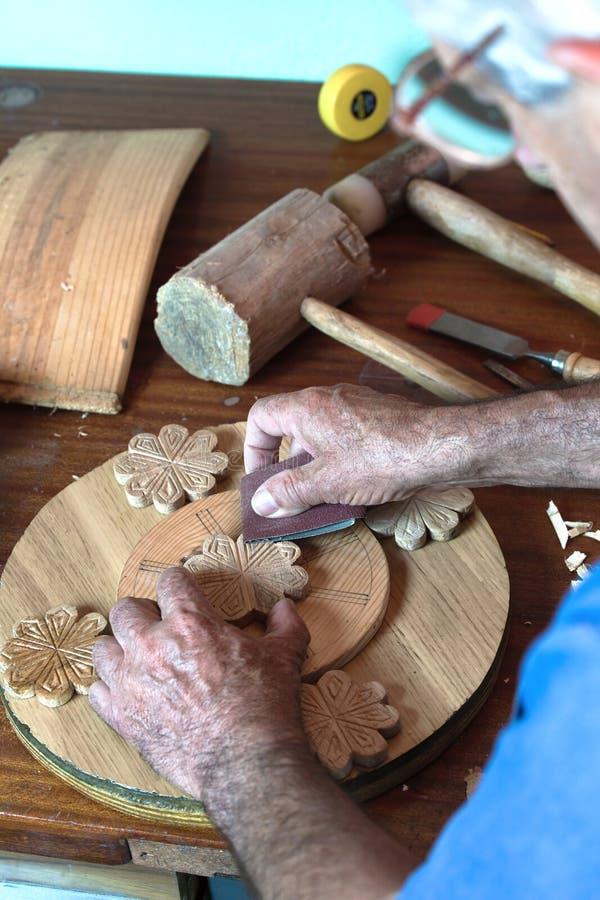 Mains verticales d'ébéniste de portrait utilisant le papier sablé sur un morceau de bois photos libres de droits