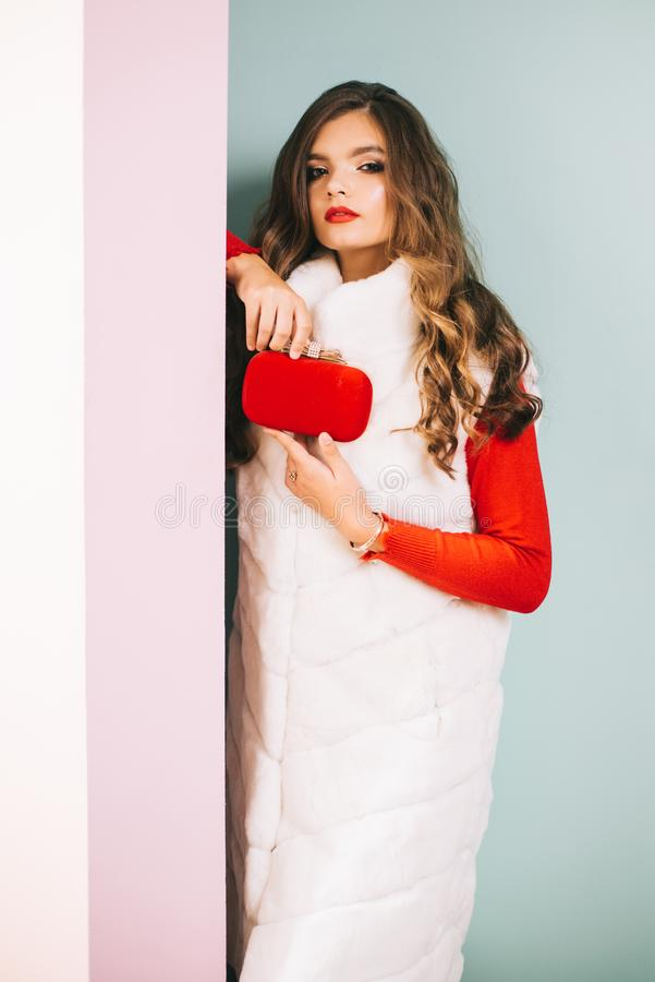 Maintaining a flawless finish. Pretty woman carry box clutch bag. Fashion girl wear glamorous fur vest with red clutch. Bag. Young woman wear elegant winter stock photography