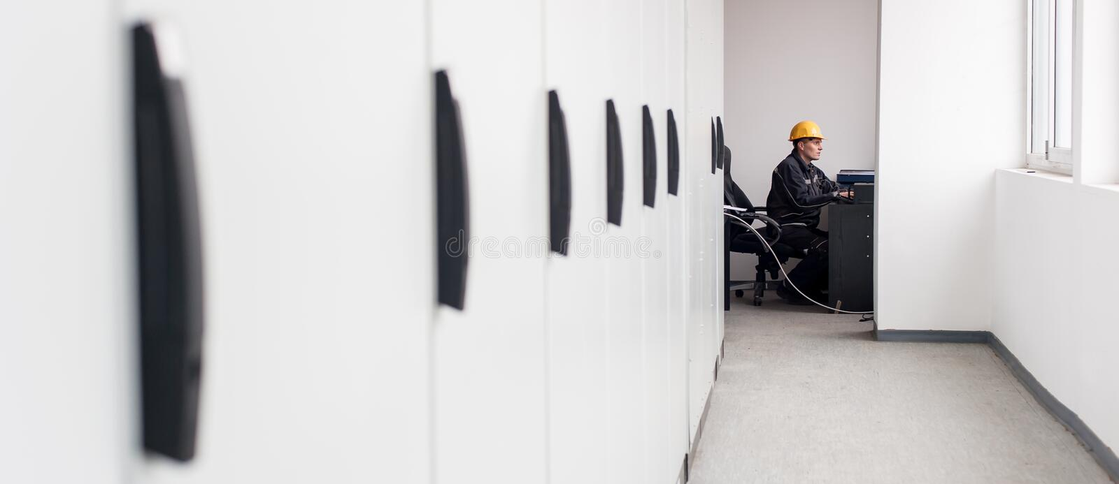 Maintenance engineer inspect relay protection system with laptop stock photography