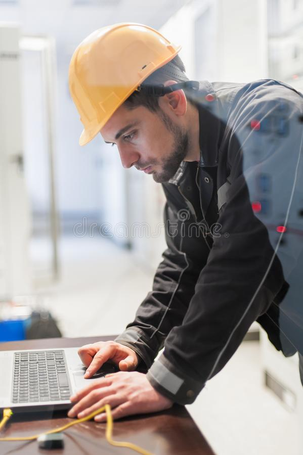 Maintenance engineer inspect relay protection system with laptop. Computer. Bay control unit. Medium voltage switchgear royalty free stock image