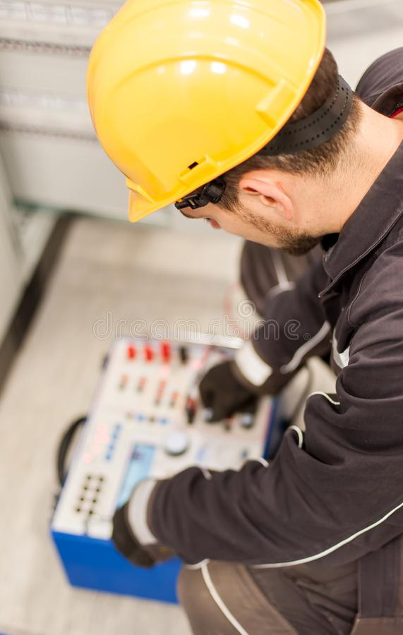 Maintenance engineer inspect system with relay test set equipment. Relay and protection testing stock image