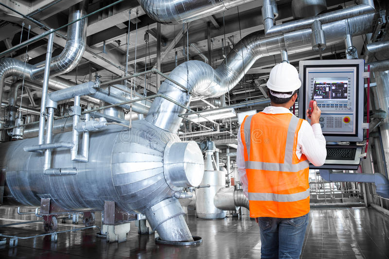 Maintenance engineer looking at monitor control in thermal power. Plant factory stock images