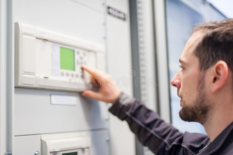 Maintenance engineer testing voltage switchgear and bay control. Maintenance engineer testing medium voltage switchgear and bay control unit. Relay protection royalty free stock image