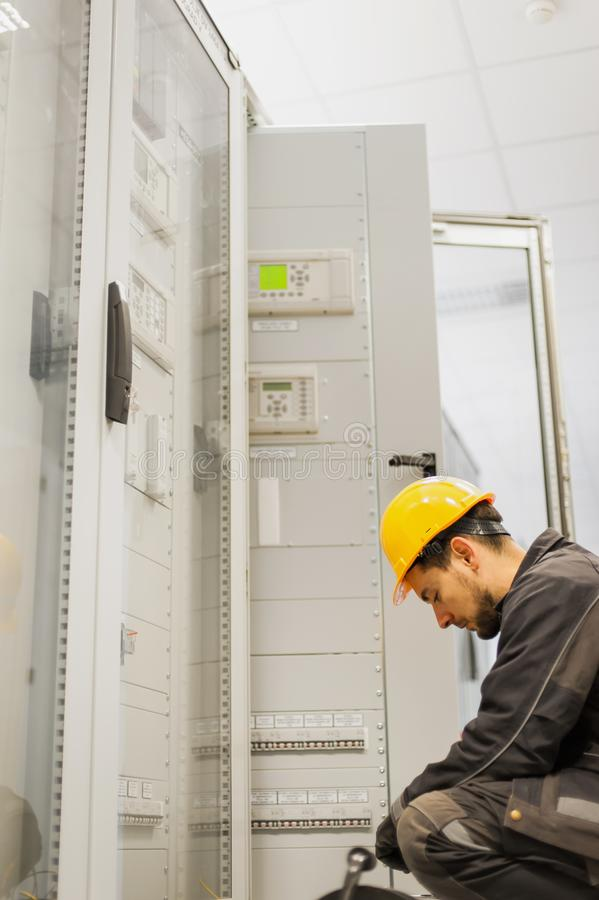 Maintenance engineer testing voltage switchgear and bay control. Maintenance engineer testing medium voltage switchgear and bay control unit. Relay protection royalty free stock photo