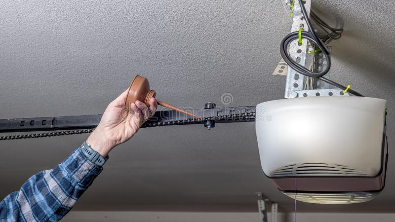 Metal oil can is used to apply some fresh oil to a garage door opener chain. Maintenance of a garage door opener chain is to add oil today stock image