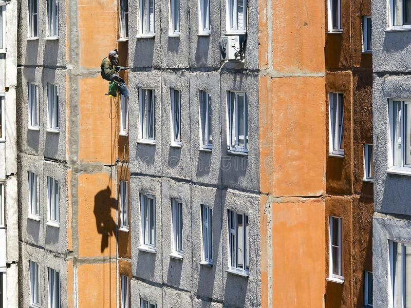 Maintenance of Joints between Precast Concrete Panels to Prevent Leakage through the Wall. Worker Climber Hanging On Ropes on a stock photos