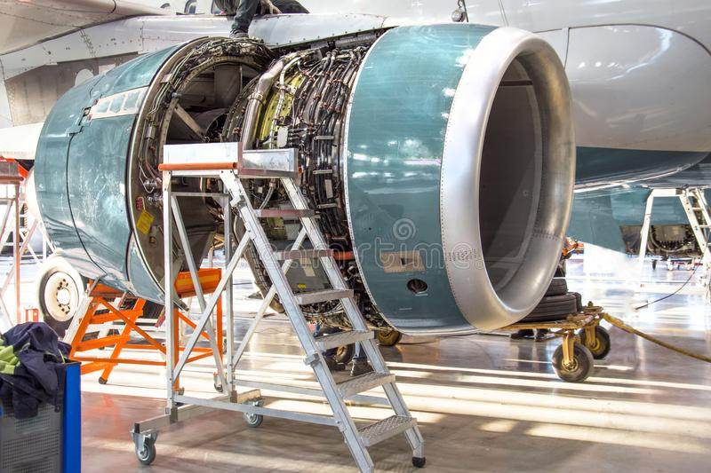 Maintenance, opened aircraft engine in the hangar in huge industrial hall royalty free stock photo