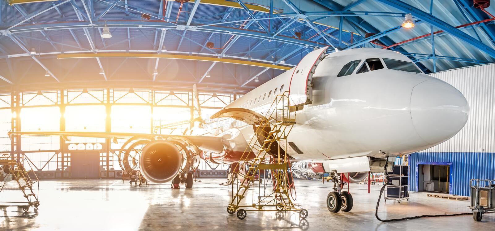 Maintenance and repair of aircraft in the aviation hangar of the airport, view of a wide panorama stock image