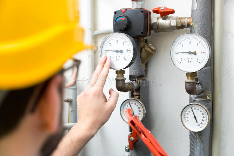 Maintenance - technician checking heating pressure meters royalty free stock photo