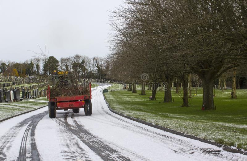 A maintenance tractor carrying wood debris to be composted at the local cemetary in Bangor county down Northern ireland stock images