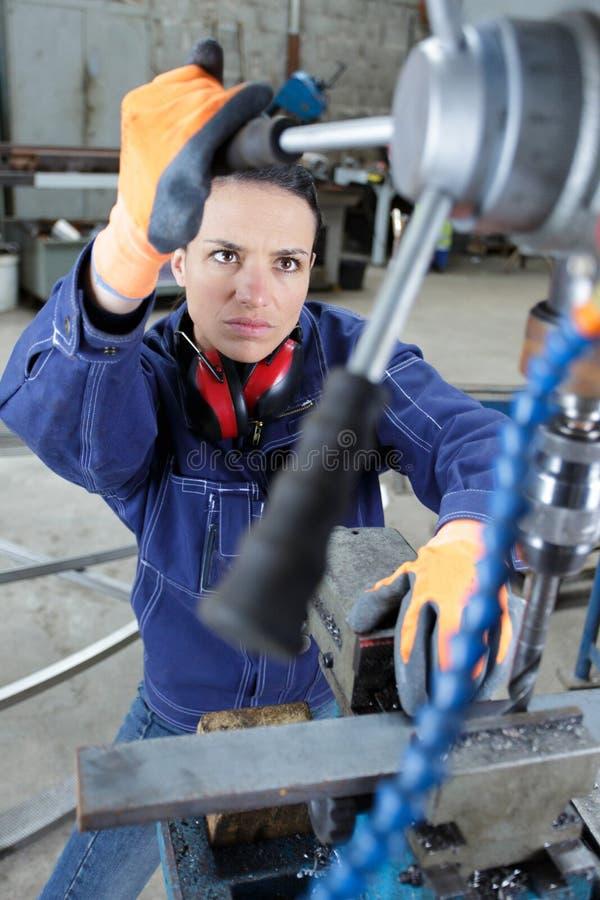 Maintenance woman using machine in factory royalty free stock photo