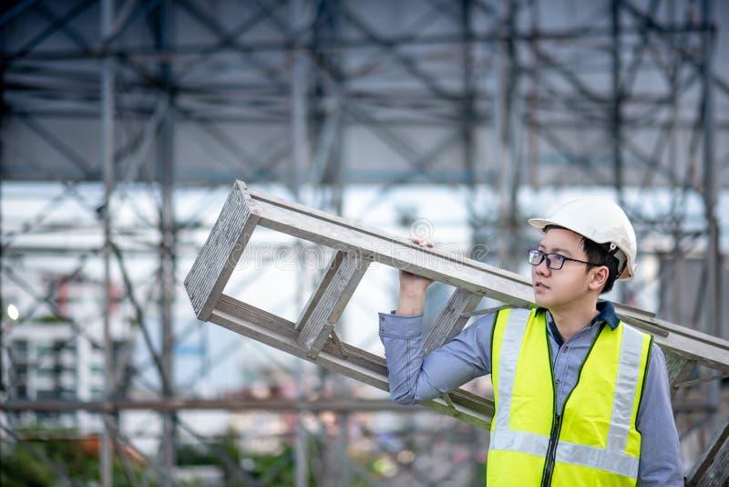 Maintenance worker man carrying aluminium ladder stock images