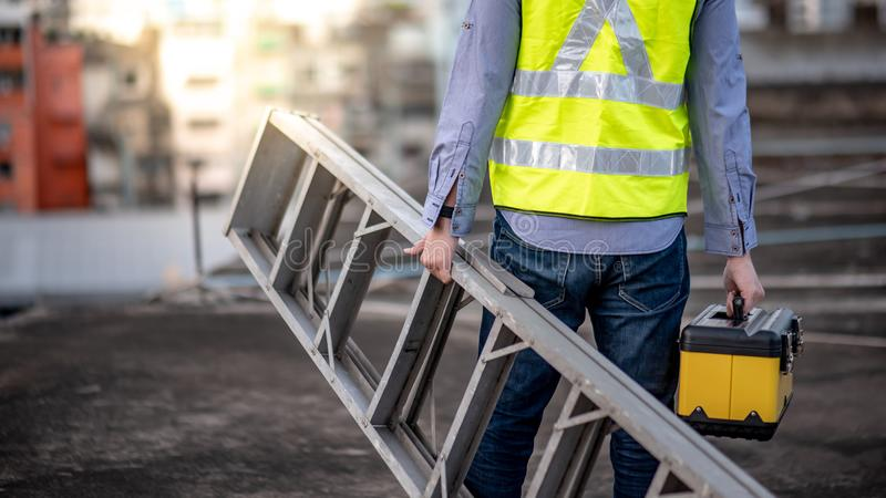 Worker man carrying aluminium ladder and tool box stock images