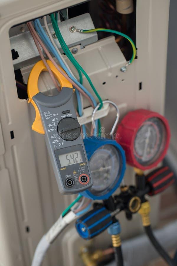 Maintenez le mètre d'ampère, mètre d'ampère de bride d'utilisation d'électricien pour le contrôle ou mesurer le courant du systèm images libres de droits