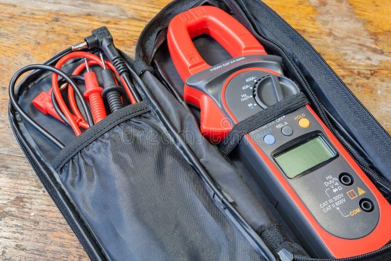 Maintenez le multimètre avec des accessoires sur une table dans un atelier photographie stock