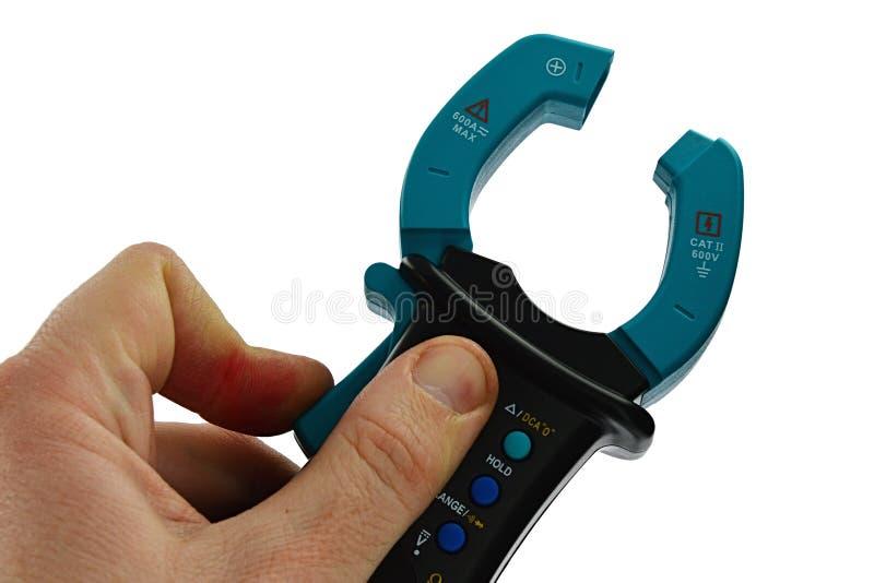 Maintenez le multimètre avec des mâchoires de transformateur ouvertes, tenu dans la main gauche sur le fond blanc photos stock