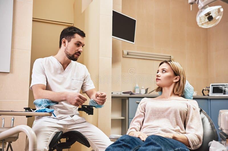 Maintenez vos dents lumineuses et fraîches Le dentiste explique en détail le progrès du traitement dentaire patient dans moderne photo libre de droits