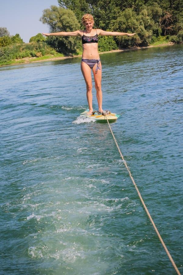 Maintining jämvikt för flicka på en surfingbräda arkivbilder