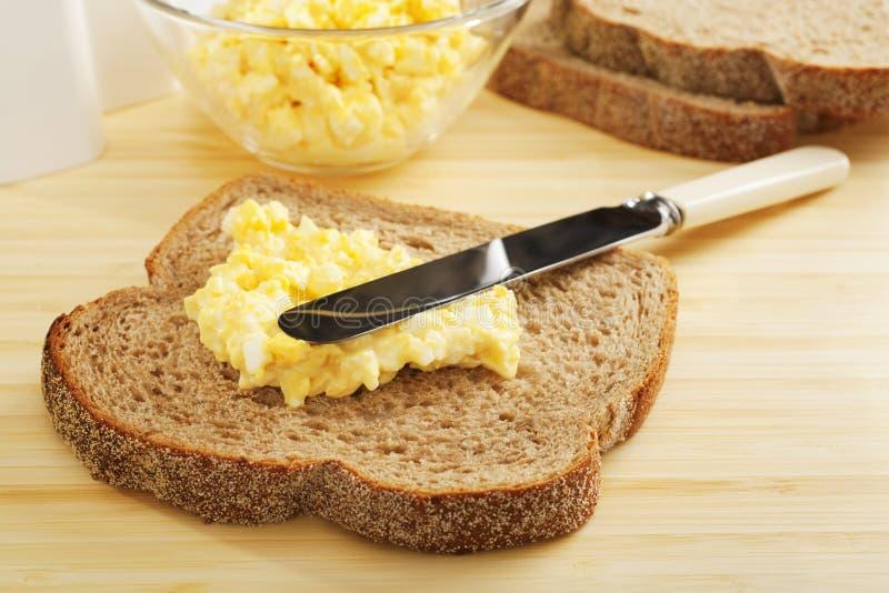 Maionese do ovo que está sendo espalhada no pão fotos de stock