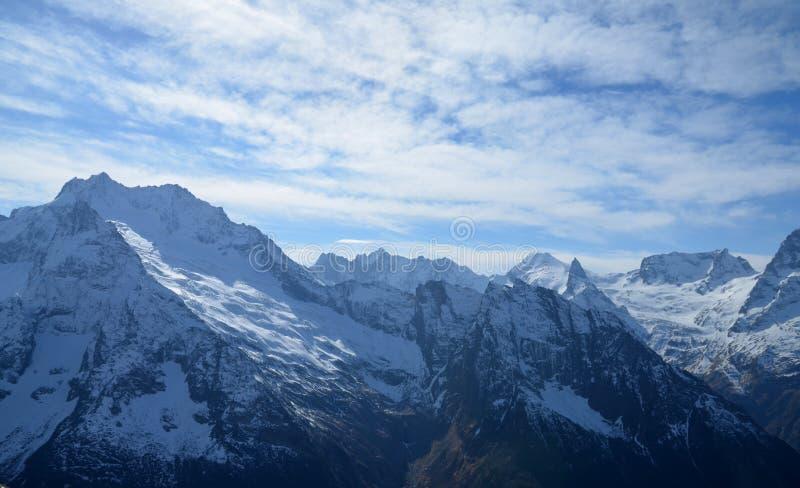 Maiores montanhas de Cáucaso cobertos de neve no dia ensolarado do inverno foto de stock