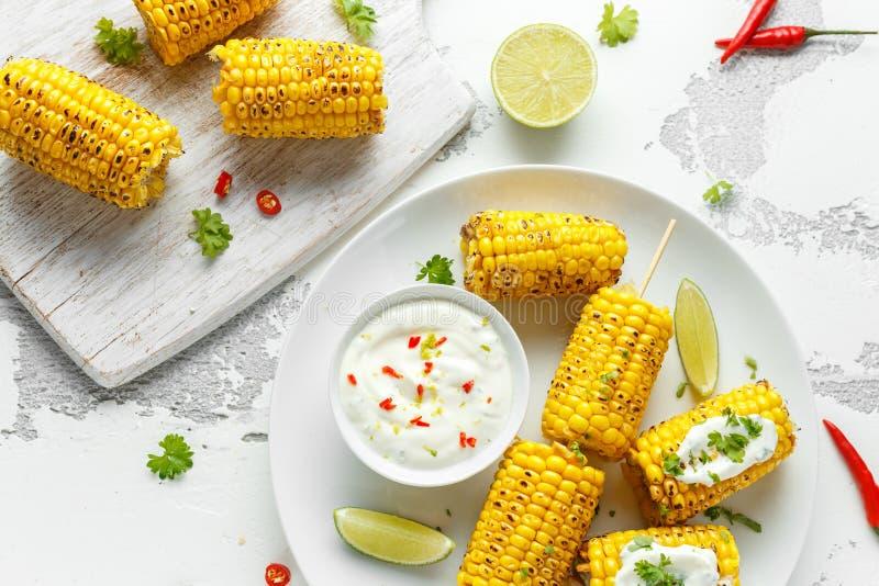 Mais arrostito con salsa, i peperoncini rossi e la calce messicani bianchi Alimento sano di estate immagine stock