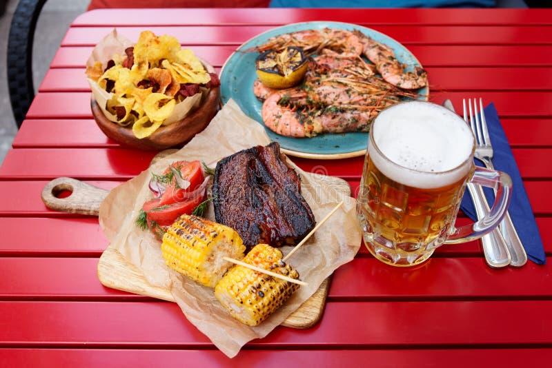 Mais arrostito e costole di carne di maiale affumicate con birra immagini stock