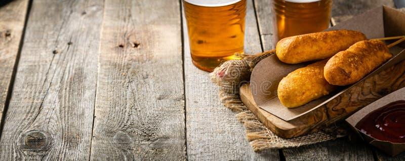 Maishunde und -bier auf rustikalem Hintergrund lizenzfreie stockfotos