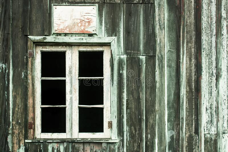 Maison abandonnée avec le vieux mur en bois gris et vert d'épluchage et la fenêtre blanche cassée grunge sans verres image stock