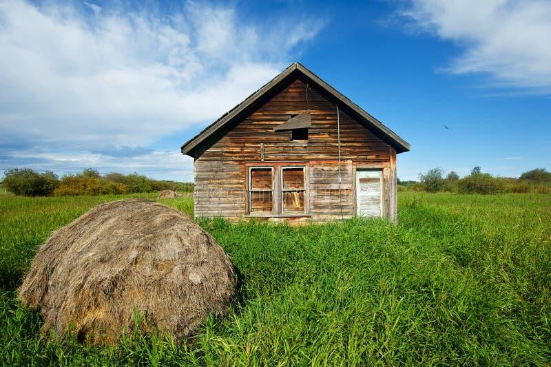 Maison abandonnée dans le domaine herbeux avec la balle de foin dans l'avant photo stock