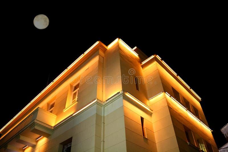 Maison allumée et la lune au-dessus de elle images libres de droits