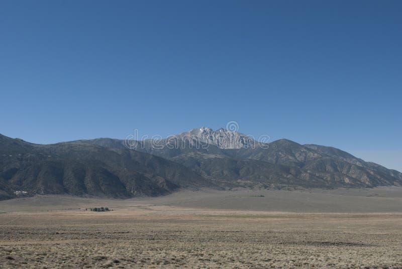 Maison au pied des montagnes Chaîne et vallée de montagnes image stock