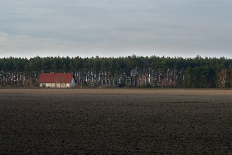 Maison blanche avec le toit rouge par le champ image stock