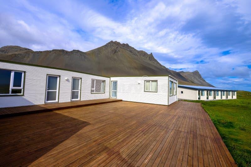 Maison blanche avec porche en bois près d'un champ gazonné et de montagnes sous un ciel nuageux photographie stock