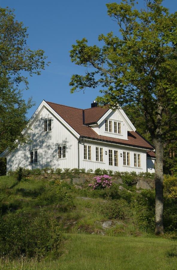 Maison blanche dans le jardin abondant photo libre de droits