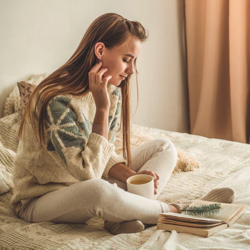 Maison confortable La belle fille lit un livre sur le lit bonjour avec le thé Détente de fille assez jeune Le concept de la lectu images stock