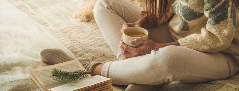 Maison confortable La belle fille lit un livre sur le lit bonjour avec le thé Détente de fille assez jeune Le concept de la lectu photographie stock libre de droits