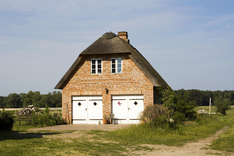 Maison couverte de chaume de ferme dans le pays photo stock