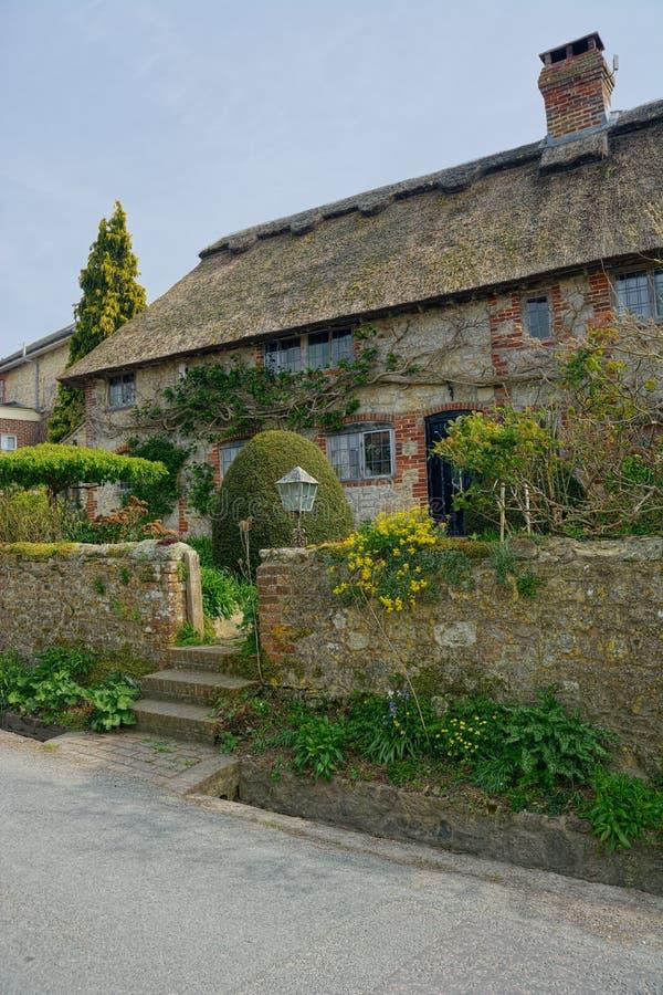 Maison couverte couverte de chaume Muret en pierre photo stock