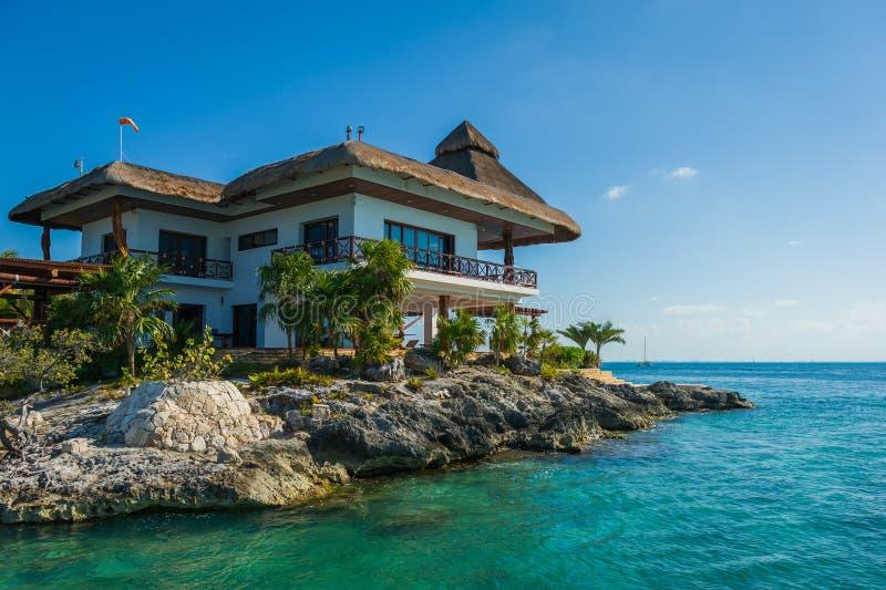 Maison couverte de chaume sur les roches par la mer photos stock