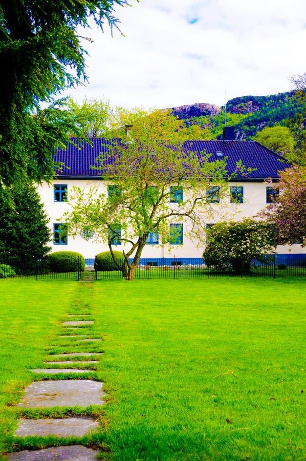 Maison d'hôtes avec la pelouse et le Rocky Path verts, Norvège photo libre de droits