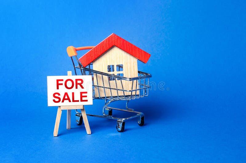 Maison dans un panier et un panneau de chevalet étiqueté pour la vente Achat et vente de biens immobiliers, d'offres à chaud et d photographie stock