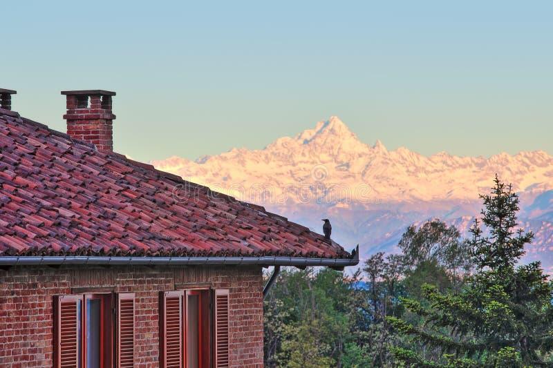 Maison de brique et montagnes neigeuses en Italie. photos stock
