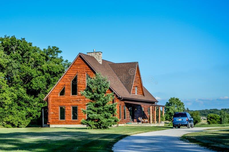 Maison de carlingue de rondin avec le véhicule bleu images stock
