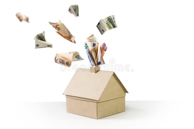 Maison de carton avec d'euro billets de banque cuisant à la vapeur hors de la cheminée photographie stock libre de droits