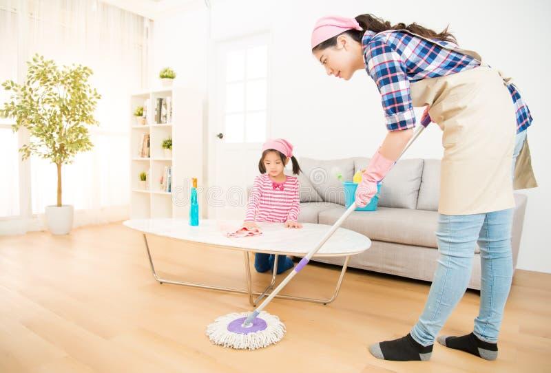 Maison de enseignement de nettoyage de fille de maman image stock
