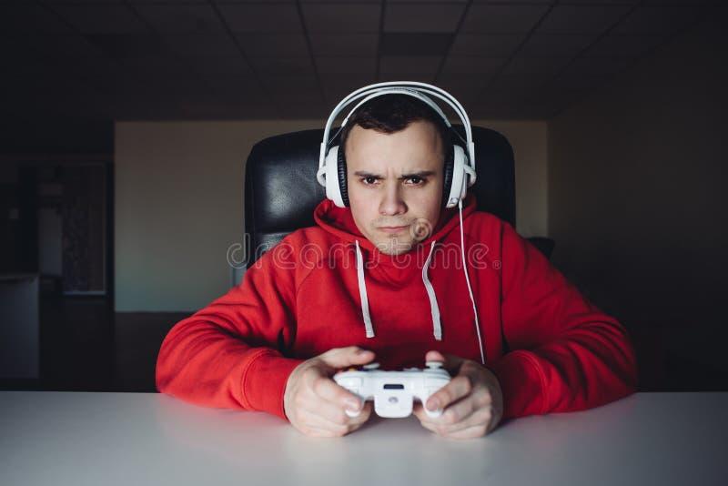 Maison de jeune homme et les jeux de jouer sur la manette Le Gamer joue des jeux d'ordinateur utilisant un gamepad photo libre de droits