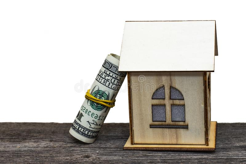 Maison de jouet avec des clés et argent liquide sur le vieux conseil en bois, sur le fond d'isolement blanc image libre de droits